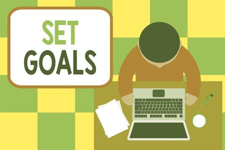Conceptual hand writing showing Set Goals. Concept meaning Defining or achieving something in the future based on plan Upper view young man sitting table laptop coffee cup pen