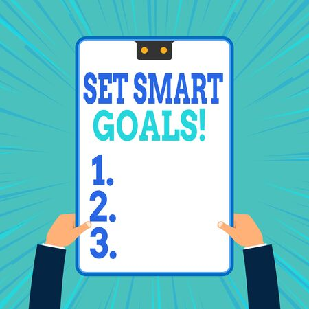 Conceptual hand writing showing Set Smart Goals. Concept meaning list to clarify your ideas focus efforts use time wisely Two male hands holding electronic device geometrical background