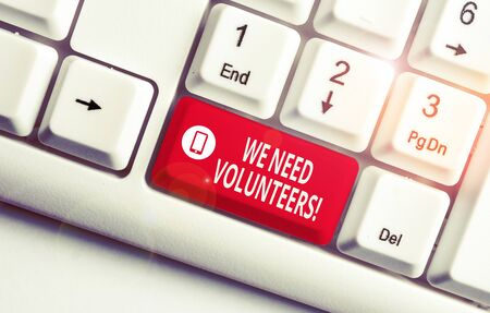 Text sign showing We Need Volunteers. Business photo text someone who does work without being paid for it White pc keyboard with empty note paper above white background key copy space