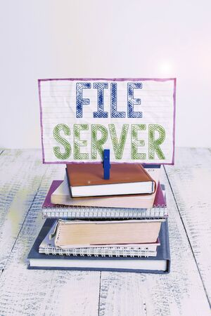 Word writing text File Server. Business photo showcasing device which controls access to separately stored data pile stacked books notebook pin clothespin colored reminder white wooden