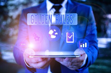 Word writing text Golden Rules. Business photo showcasing Basic principle that should be followed Important Principle Male human wear formal work suit presenting presentation using smart device 写真素材