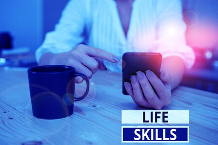 Text sign showing Life Skills. Business photo showcasing that is necessary or desirable full participation in everyday woman using smartphone office supplies technological devices inside home