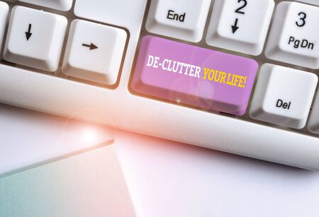 Word writing text De Clutter Your Life. Business photo showcasing remove unnecessary items from untidy or overcrowded places White pc keyboard with empty note paper above white background key copy spa 写真素材