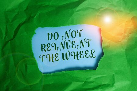 Text sign showing Do Not Reinvent The Wheel. Business photo text stop duplicating a basic method previously done Green crumpled ripped colored paper sheet centre torn colorful background Фото со стока