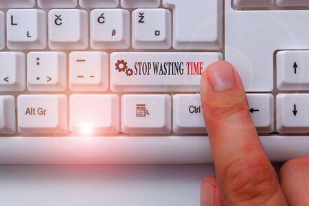 Conceptual hand writing showing Stop Wasting Time. Concept meaning advising demonstrating or group start planning and use it White pc keyboard with note paper above the white background