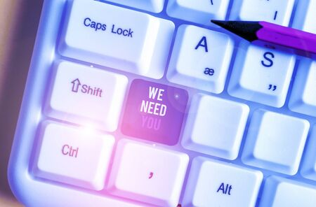 Writing note showing We Need You. Business concept for asking someone to work together for certain job or target White pc keyboard with note paper above the white background Banco de Imagens