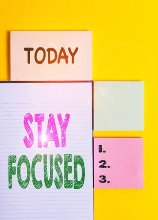 Word writing text Stay Focused. Business photo showcasing Be attentive Concentrate Prioritize the task Avoid distractions Colored empty papers with copy space on the yellow background table