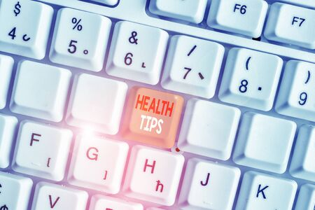 Writing note showing Health Tips. Business concept for advice or information given to be helpful in being healthy White pc keyboard with note paper above the white background