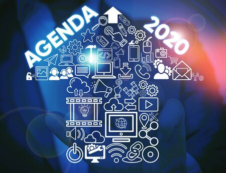 Writing note showing Agenda 2020. Business concept for list of activities in order which they are to be taken up Male wear formal work suit presenting presentation smart device
