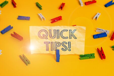 Writing note showing Quick Tips. Business concept for small but particularly useful piece of practical advice Colored clothespin papers empty reminder yellow floor background office