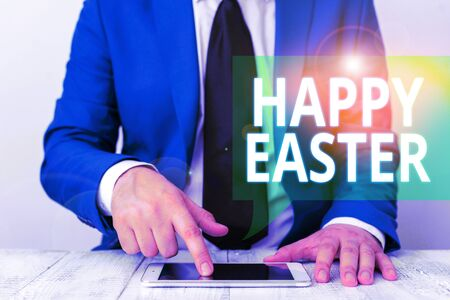 Conceptual hand writing showing Happy Easter. Concept meaning Christian feast commemorating the resurrection of Jesus Businessman in blue suite with a tie holds lap top in hands