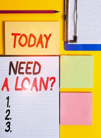 Conceptual hand writing showing Need A Loan Question. Concept meaning asking he need money expected paid back with interest Empty papers with copy space on yellow background table