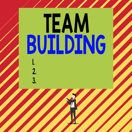 Text sign showing Team Building. Business photo showcasing various types of activities used to enhance social relations Short hair immature young man stand in front of rectangle big blank board