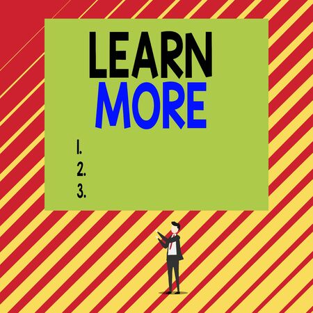 Text sign showing Learn More. Business photo showcasing knowledge or skill acquired by instruction Considerable learning Short hair immature young man stand in front of rectangle big blank board