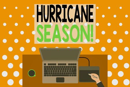 Word writing text Hurricane Season. Business photo showcasing time when most tropical cyclones are expected to develop Upper view laptop wooden desk worker drawing tablet coffee cup office