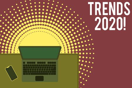 Handwriting text writing Trends 2020. Conceptual photo general direction in which something is developing or changing Upper view office working place laptop lying wooden desk smartphone side