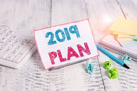 Text sign showing 2019 Plan. Business photo showcasing setting up your goals and plans for the current year or in 2019 Notepaper stand on buffer wire in between computer keyboard and math sheets 写真素材 - 132223374