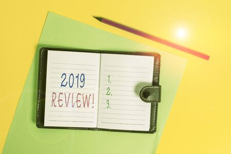 Text sign showing 2019 Review. Business photo showcasing remembering past year events main actions or good shows Dark leather private locked diary striped sheets marker colored background