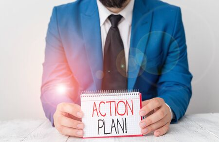 Writing note showing Action Plan. Business concept for proposed strategy or course of actions for certain time Man holds empty paper with copy space in front of him Space