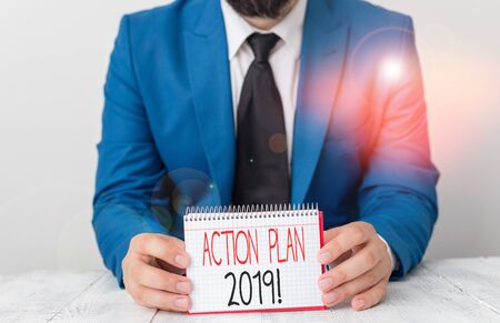 Writing note showing Action Plan 2019. Business concept for proposed strategy or course of actions for current year Man holds empty paper with copy space in front of him Space