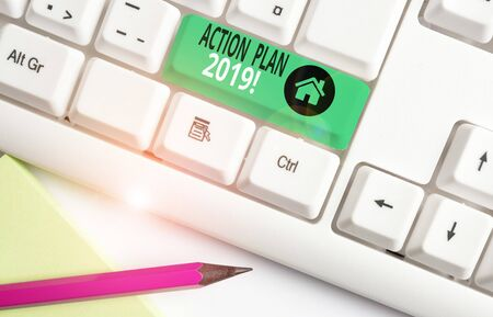 Handwriting text writing Action Plan 2019. Conceptual photo proposed strategy or course of actions for current year White pc keyboard with empty note paper above white background key copy space Banco de Imagens - 132232802