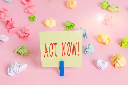 Writing note showing Act Now. Business concept for do not hesitate and start working or doing stuff right away Colored crumpled papers empty reminder pink floor background clothespin 写真素材