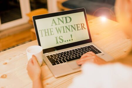 Handwriting text writing And The Winner Is. Conceptual photo announcing who got first place at competition or exam woman laptop computer smartphone mug office supplies technological devices Stok Fotoğraf