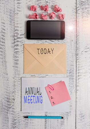Handwriting text writing Annual Meeting. Conceptual photo yearly meeting of the general membership of an organization Envelop smartphone notepad note clip marker paper balls wooden background Stok Fotoğraf