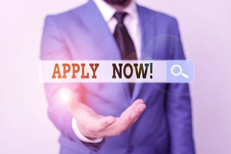 Writing note showing Apply Now. Business concept for request something officially in writing or by sending in form Man in front of table. Mobile phone and notes on the table