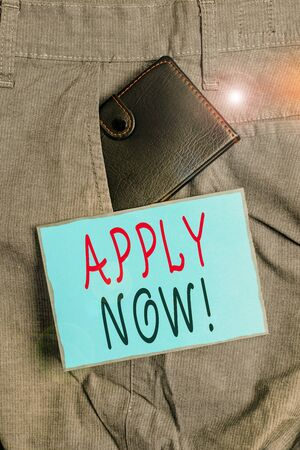 Conceptual hand writing showing Apply Now. Concept meaning request something officially in writing or by sending in form Small wallet inside trouser front pocket near notation paper