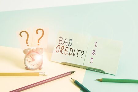 Writing note showing Bad Creditquestion. Business concept for inabilityof a demonstrating to repay a debt on time and in full Mini size alarm clock beside stationary on pastel backdrop