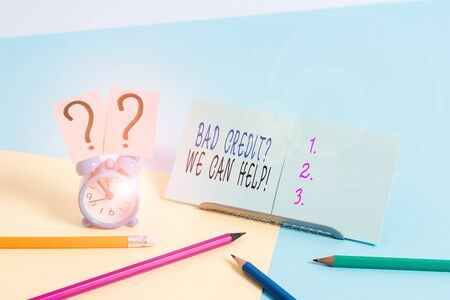 Writing note showing Bad Creditquestion We Can Help. Business concept for offerr help to gain positive payment history Mini size alarm clock beside stationary on pastel backdrop Imagens