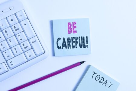 Text sign showing Be Careful. Business photo showcasing making sure of avoiding potential danger mishap or harm White pc keyboard with empty note paper and pencil above white background
