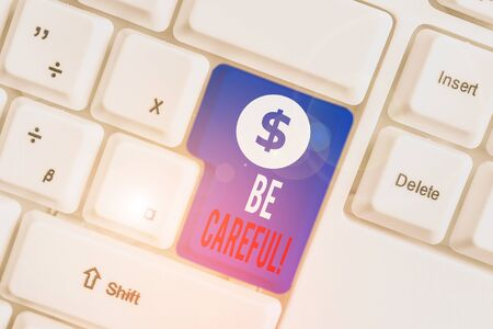 Text sign showing Be Careful. Business photo text making sure of avoiding potential danger mishap or harm White pc keyboard with empty note paper above white background key copy space Banco de Imagens