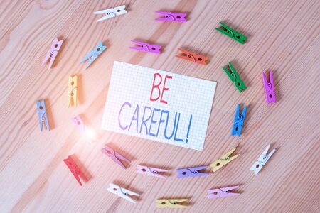 Text sign showing Be Careful. Business photo text making sure of avoiding potential danger mishap or harm Colored clothespin papers empty reminder wooden floor background office