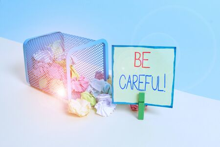 Conceptual hand writing showing Be Careful. Concept meaning making sure of avoiding potential danger mishap or harm Trash bin crumpled paper clothespin reminder office supplies Stock fotó