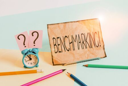 Writing note showing Benchmarking. Business concept for evaluate something by comparison with standard or scores Mini size alarm clock beside stationary on pastel backdrop Stok Fotoğraf