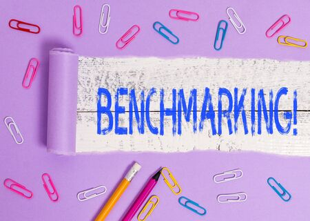Text sign showing Benchmarking. Business photo showcasing evaluate something by comparison with standard or scores Stationary and torn cardboard placed above a wooden classic table backdrop