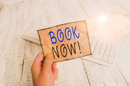 Conceptual hand writing showing Book Now. Concept meaning guaranteed to have place because you have already purchased it Man holding colorful reminder square shaped paper wood floor