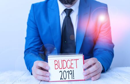 Writing note showing Budget 2019. Business concept for estimate of income and expenditure for current year Man holds empty paper with copy space in front of him Space 写真素材 - 132245509
