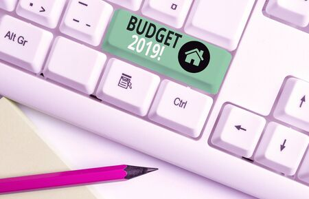 Handwriting text writing Budget 2019. Conceptual photo estimate of income and expenditure for current year White pc keyboard with empty note paper above white background key copy space 写真素材 - 132245368