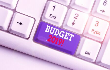 Text sign showing Budget 2019. Business photo text estimate of income and expenditure for current year White pc keyboard with empty note paper above white background key copy space