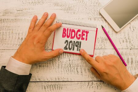 Text sign showing Budget 2019. Business photo text estimate of income and expenditure for current year Hand hold note paper near writing equipment and modern smartphone device