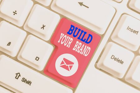 Handwriting text writing Build Your Brand. Conceptual photo enhancing brand equity using advertising campaigns White pc keyboard with empty note paper above white background key copy space