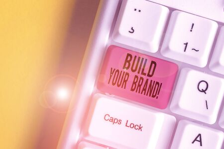 Word writing text Build Your Brand. Business photo showcasing creates or improves customers knowledge and opinions of product White pc keyboard with empty note paper above white background key copy space