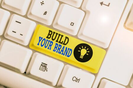 Text sign showing Build Your Brand. Business photo showcasing enhancing brand equity using advertising campaigns White pc keyboard with empty note paper above white background key copy space Stok Fotoğraf