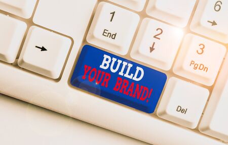 Text sign showing Build Your Brand. Business photo text creates or improves customers knowledge and opinions of product White pc keyboard with empty note paper above white background key copy space