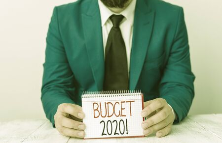 Writing note showing Budget 2020. Business concept for estimate of income and expenditure for next or current year Man holds empty paper with copy space in front of him Space 写真素材