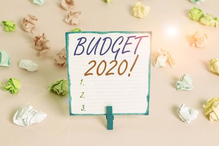 Handwriting text Budget 2020. Conceptual photo estimate of income and expenditure for next or current year Colored crumpled papers empty reminder pink floor background clothespin