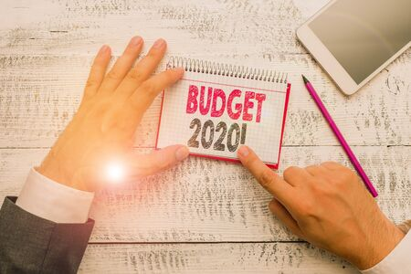 Text sign showing Budget 2020. Business photo text estimate of income and expenditure for next or current year Hand hold note paper near writing equipment and modern smartphone device 写真素材 - 132244922
